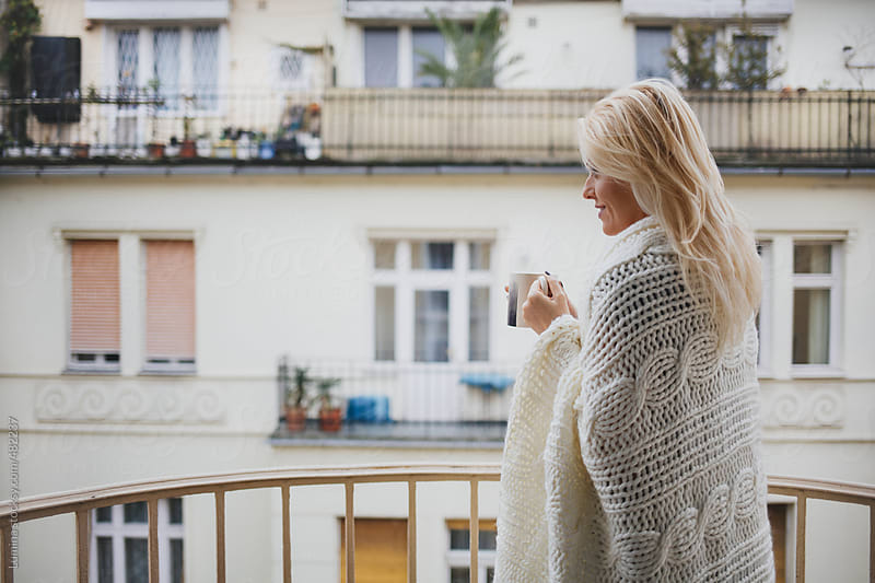 Blonde Woman Wrapped in a Blanket Drinking Tea on a Balcony by Lumina for Stocksy United
