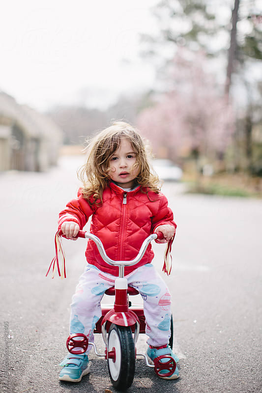 Cute toddler riding a tricycle on a street by Jakob for Stocksy United
