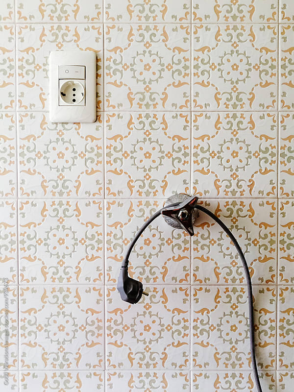 Power socket, cable and a valve on a retro tiled wall by Good Vibrations Images for Stocksy United