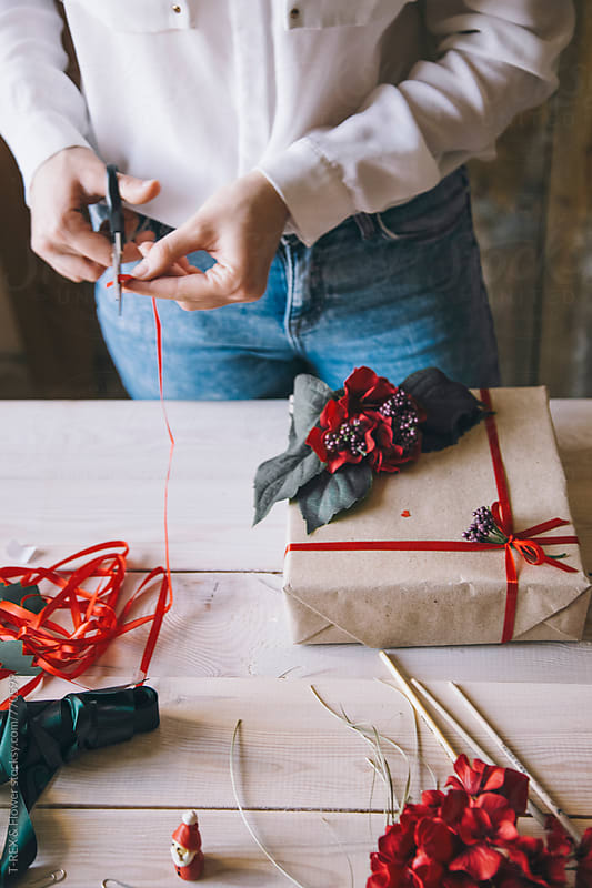 Woman decorating Christmas present with red ribbon by T-REX & Flower for Stocksy United