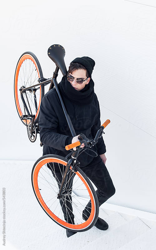 Young cyclist in black outfit walking with his bike on shoulder. by Audrey Shtecinjo for Stocksy United