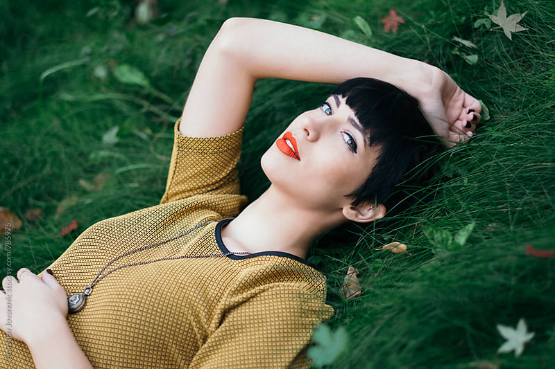Dreamy Portrait of a Young Woman Lying in the Grass by Branislav Jovanović for Stocksy United