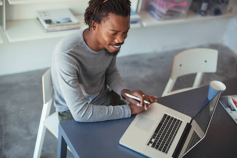 Smiling African Sitting at His Laptop by Lumina for Stocksy United