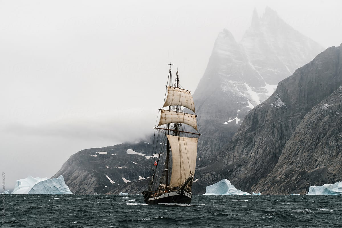 old vintage sailing vessel and icebergs floating in the arctic close