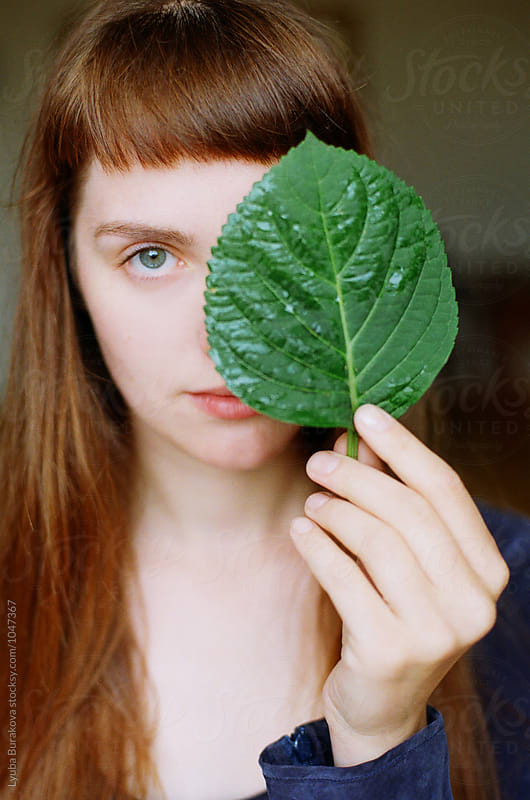 Young woman looking through green leaf by Lyuba Burakova for Stocksy United