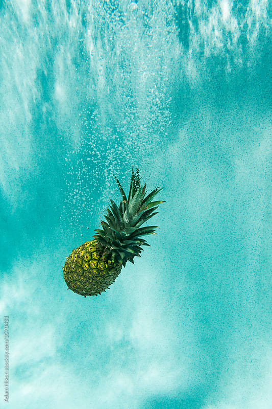 Pineapple in a swimming pool by Adam Nixon for Stocksy United
