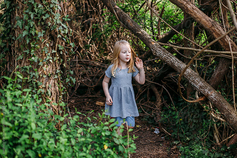 a young girl stands in the woods by Amanda Voelker for Stocksy United
