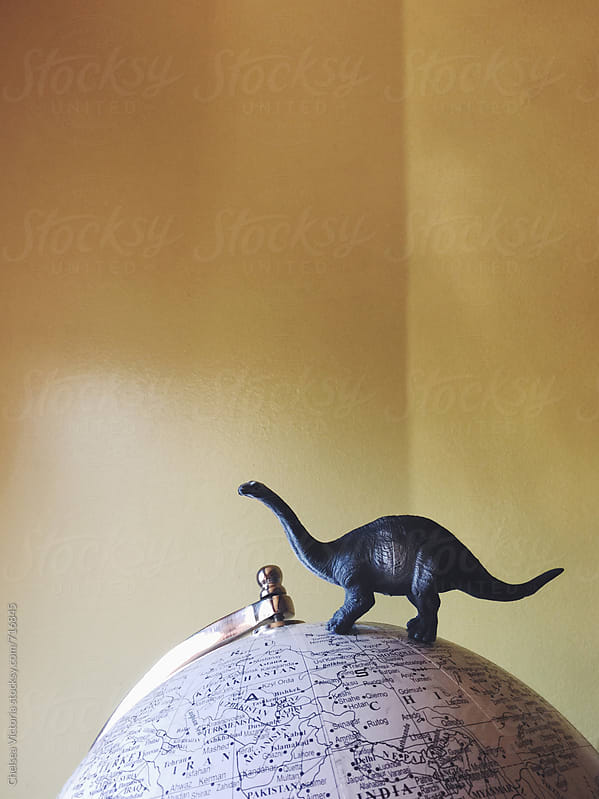 A toy dinosaur sitting on top of a globe by Chelsea Victoria for Stocksy United