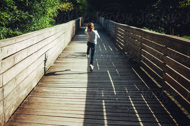 Girl jumping on a wooden bridge by Giada Canu for Stocksy United