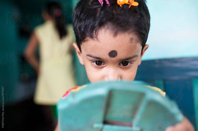 A little girl looking herself in mirror by PARTHA PAL for Stocksy United