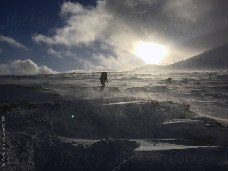 Solitary figure braving the winter mountains by Neil Warburton for Stocksy United