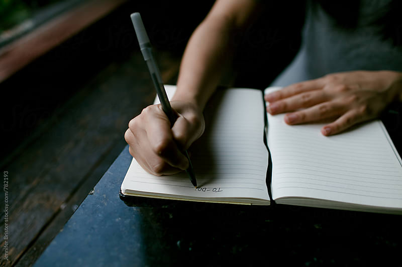Woman writing in notebook by Jennifer Brister for Stocksy United