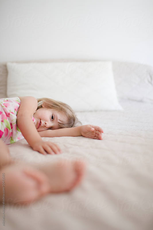 Funny little girl lying on the bed by michela ravasio for Stocksy United