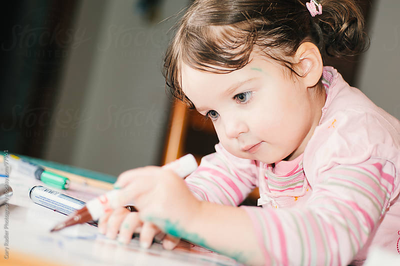 Little Girl concentrating on her Drawing by Gary Radler Photography for Stocksy United