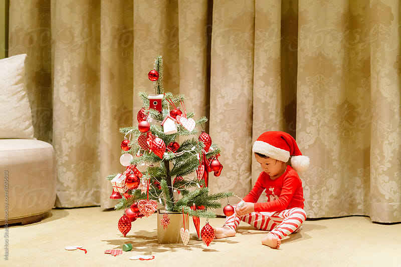 Cue girl decorating christmas tree by MaaHoo Studio for Stocksy United