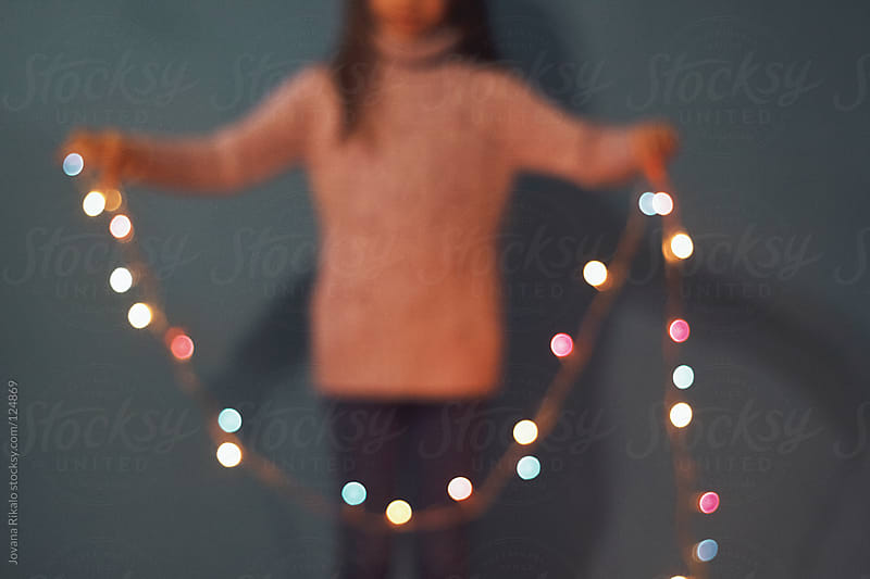Little girl holding Christmas lights,blurry image by Jovana Rikalo for Stocksy United