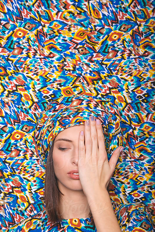 Close-up half face of woman in bright patterned turban by Danil Nevsky for Stocksy United