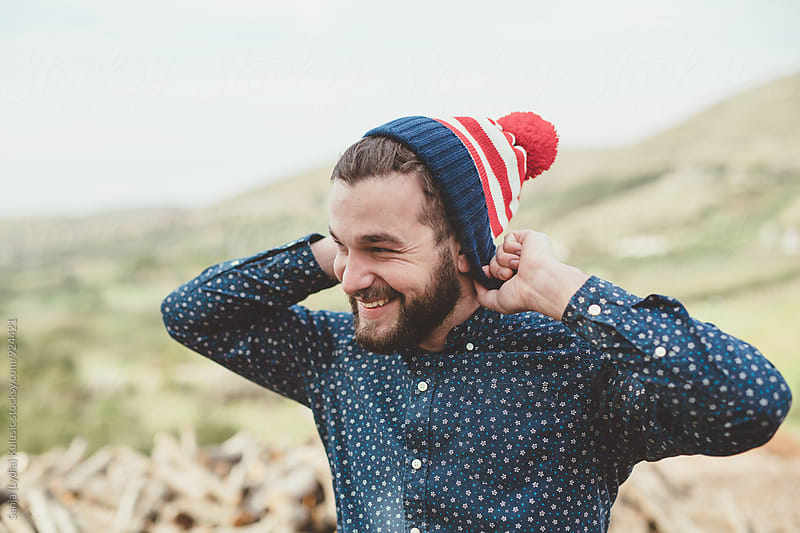 Beardy guy wears american flag winter hat by Sanja (Lydia) Kulusic for Stocksy United