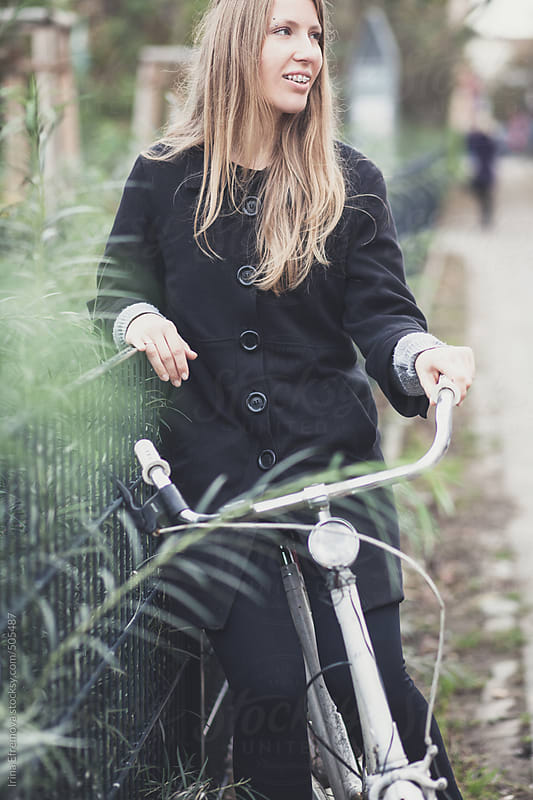 Pretty blond girl on a white bicycle by Irina Efremova for Stocksy United