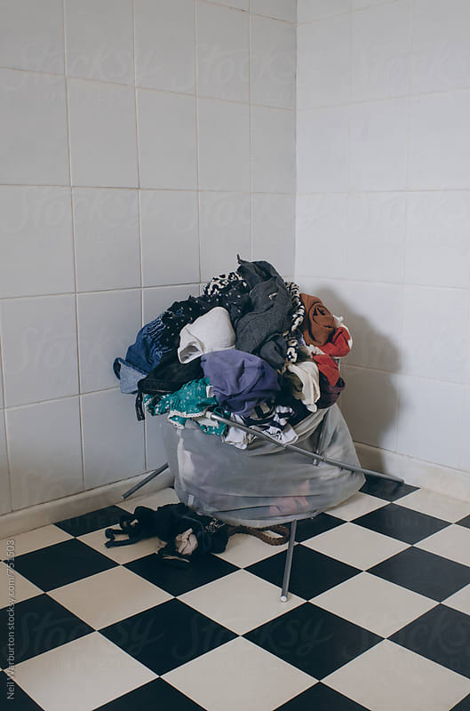 Washing basket that has collapsed under weight of clothing by Neil Warburton for Stocksy United
