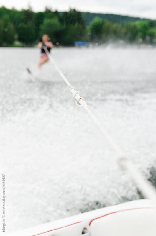 woman water skis, blurred with focus on rope  by Margaret Vincent for Stocksy United