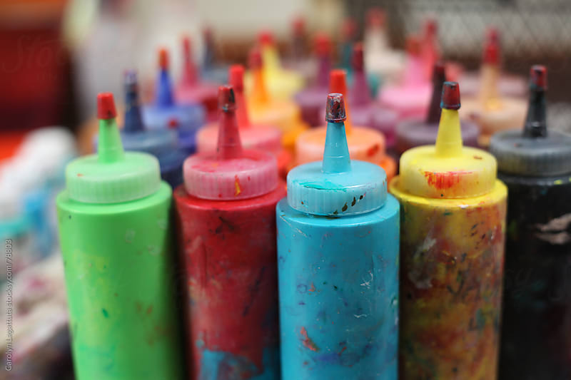 Bottles of colorful paint in an artist's studio by Carolyn Lagattuta for Stocksy United