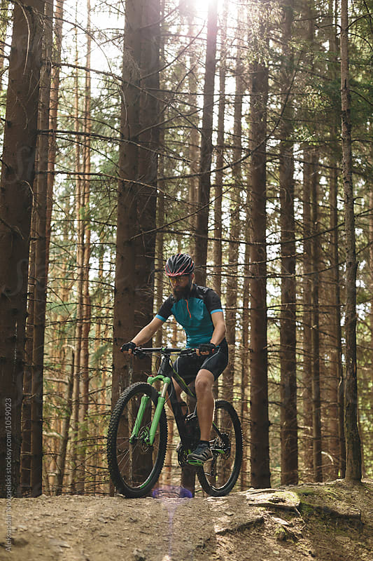 Mountain biker riding in the forest by Aleksandar Novoselski for Stocksy United