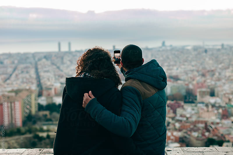 Back view of couple taking a selfie above city at sunrise. by BONNINSTUDIO for Stocksy United
