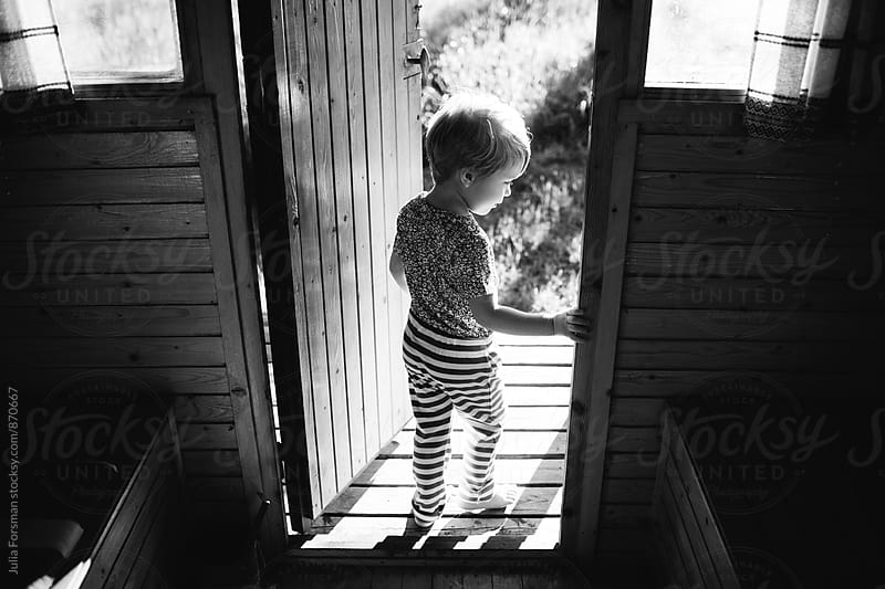 A young child steps out of a small wooden building. by Julia Forsman for Stocksy United