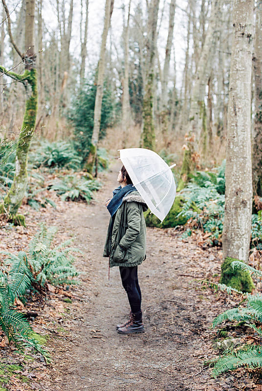 Woman in forest holding umbrella by Daniel Kim Photography for Stocksy United