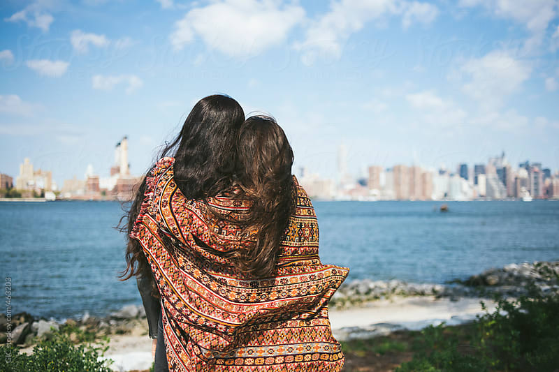 Affectionate female friends under a blanket looking NY city by GIC for Stocksy United