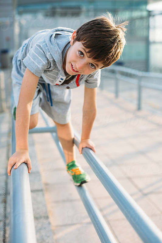 6 years old boy on metal bars playfully looking at camera by Beatrix Boros for Stocksy United