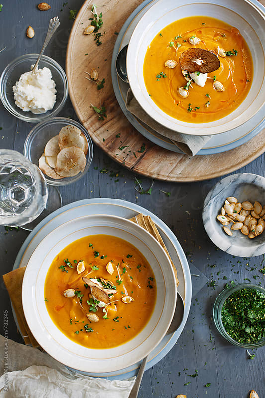 Two bowls of gourmet butternut squash soup on a table. by Darren Muir for Stocksy United