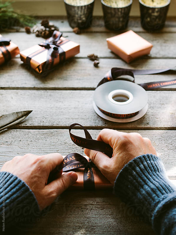 Hands wrapping Christmas gifts by Helen Rushbrook for Stocksy United