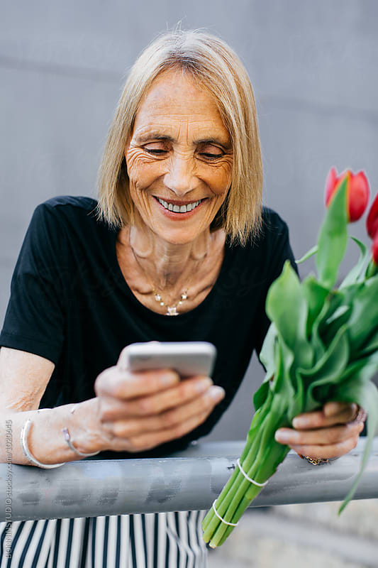 Elderly woman holding red tulips using her phone outside.  by BONNINSTUDIO for Stocksy United