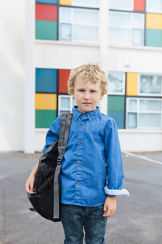 A blonde boy standing in front of a school with a backpack on his shoulder by Ania Boniecka for Stocksy United