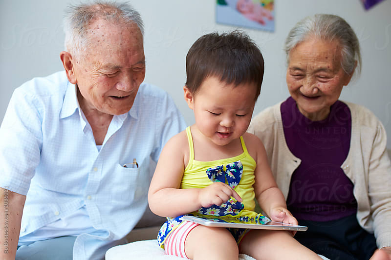 senior asian couple watch their great granddaughter using tablet by Bo Bo for Stocksy United