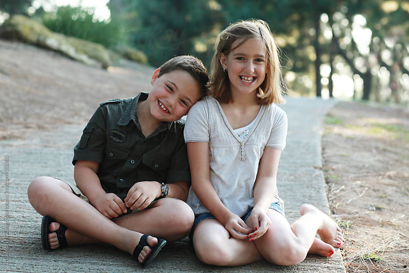 Young boy and girl leaning on each other and laughing by Dina Giangregorio for Stocksy United