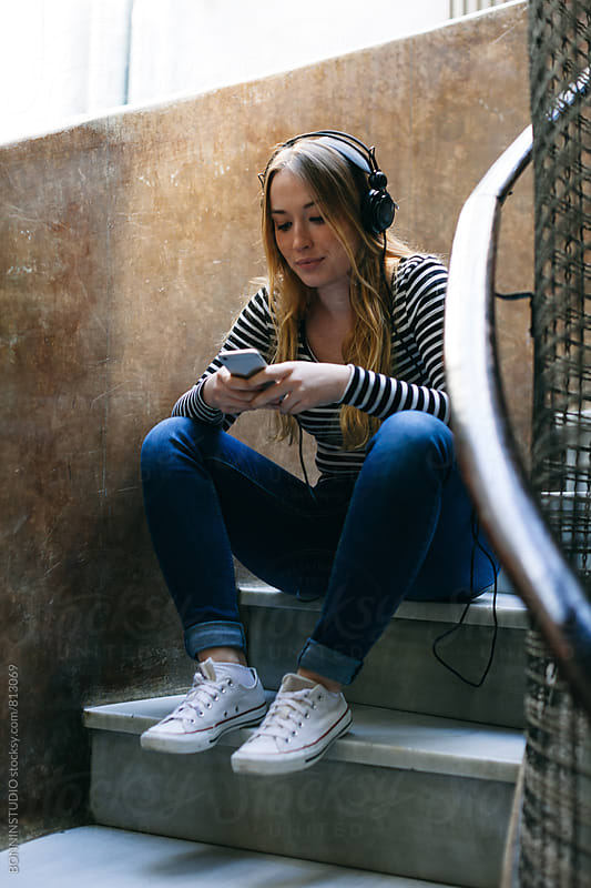 Young woman using her phone whilst listening music with headphone. by BONNINSTUDIO for Stocksy United