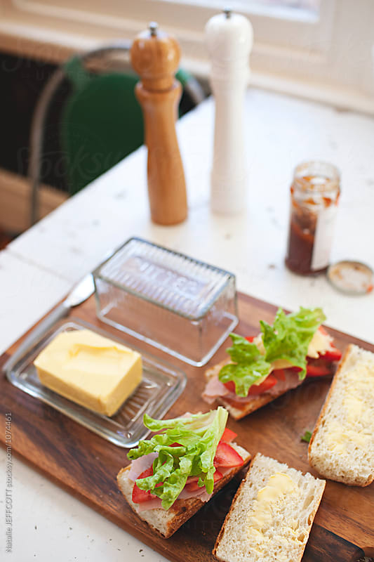 Preparing lunch at home. Baguette with butter, ham, lettuce and tomato by Natalie JEFFCOTT for Stocksy United