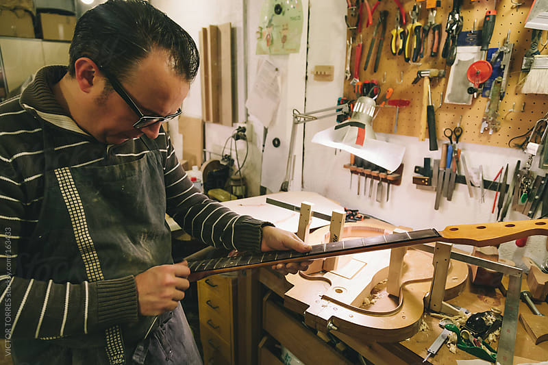 Man working at a Workshop with Musical instruments by VICTOR TORRES for Stocksy United