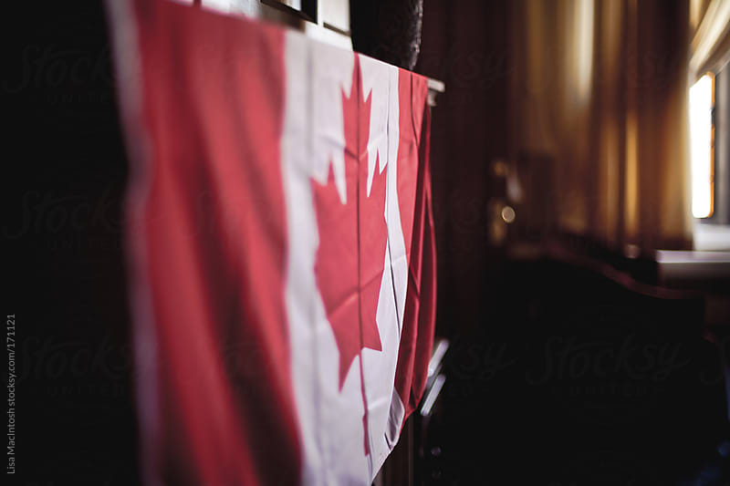 Canadian Flag draped over fireplace by Lisa MacIntosh for Stocksy United