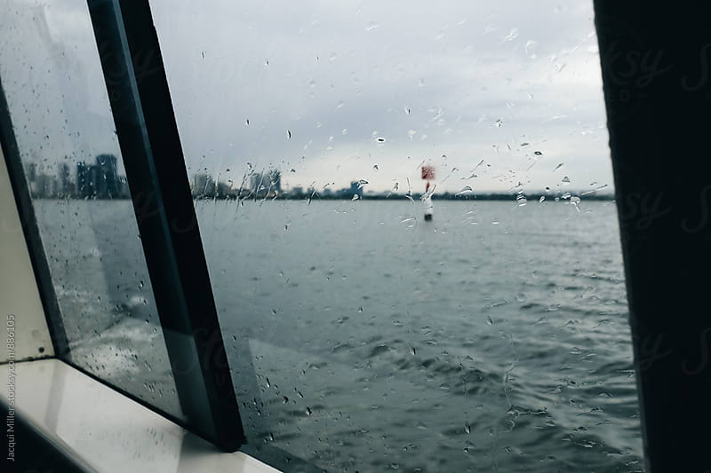 Looking through boat window toward unrecognisable city on a stormy day by Jacqui Miller for Stocksy United