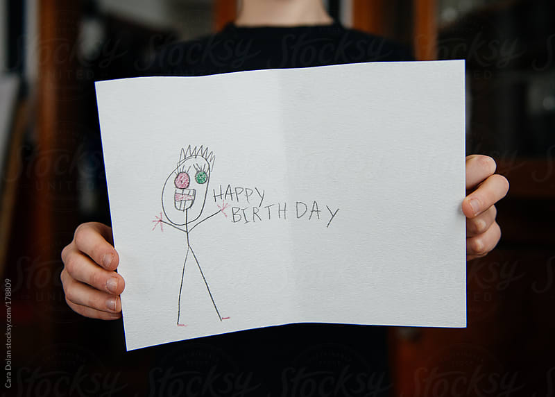 Child shows off a strange little birthday card he's made by Cara Dolan for Stocksy United