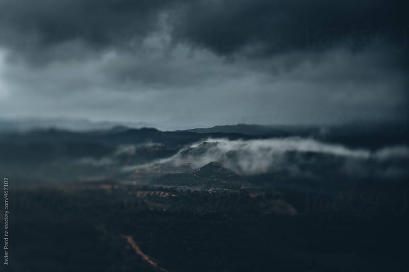 Mountains with storm clouds by Javier Pardina for Stocksy United