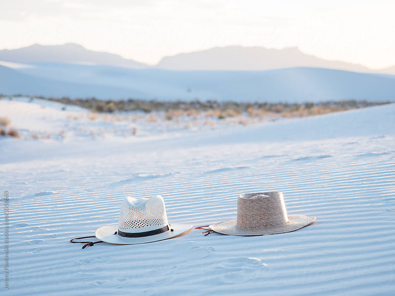Couples straw hats laying in sand with mountains in distance by Jeremy Pawlowski for Stocksy United