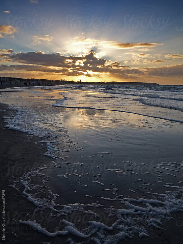 Beach at sunset with sun reflecting in water by Melanie Kintz for Stocksy United