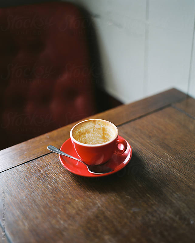 Empty red coffee cup and saucer on a wooden table in a cafe.  by Suzi Marshall for Stocksy United