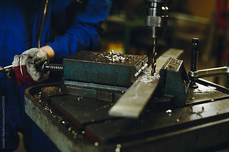detail of a metal worker drilling a metal plate by Leander Nardin for Stocksy United