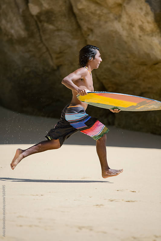 A young surfer running for the water holding his board by Ania Boniecka for Stocksy United